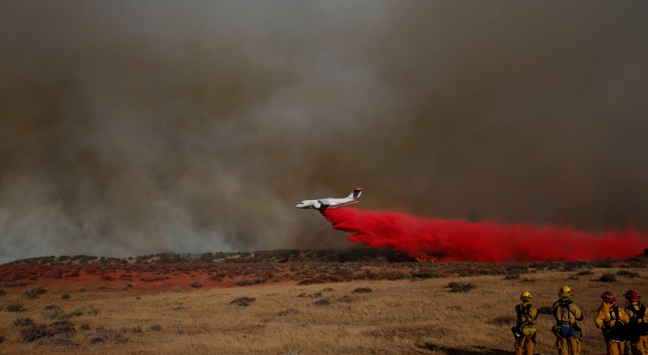 Firefighters watch from a campground as a firefighting aircraft drops fire retardant during the Pilot Fire near Silverwood Lake in San Bernardino county near Hesperia, California, U.S. August 7, 2016.  REUTERS/Patrick T Fallon
