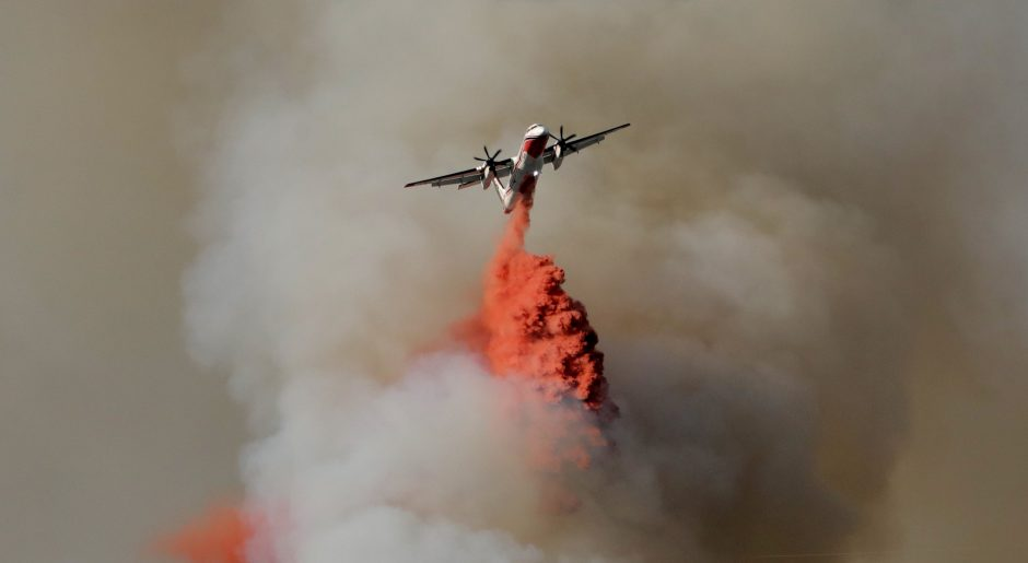 A firefighting plane drops flame retardant to extinguish a forest fire in Castagniers near Nice